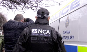 An NCA officer next to a police vehicle, as a man was arrested following raids across the north-east of England, Sussex and London in a major operation aimed at tackling people-smuggling.