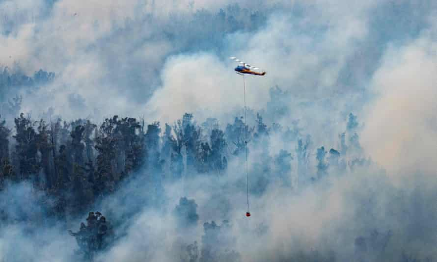 Helicopter dumping water on a fire in Victoria's East Gippsland region.