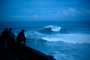 Surfers keep an eye on early-morning conditions before a free surfing session.