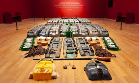 An art installation comprising items including parts of jerrycans, scales and green bottles