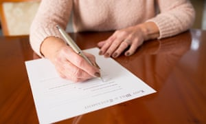 A woman signs a last will and testament at home.
