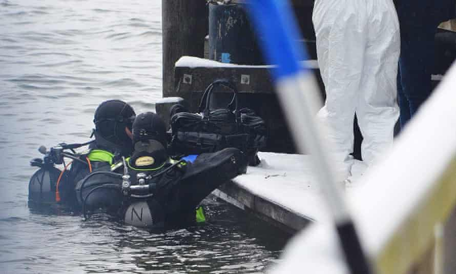 Austrian police divers retrieve a bag from the Traunsee lake in Gmunden.