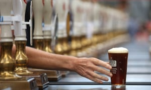 A pint of beer is passed across a bar