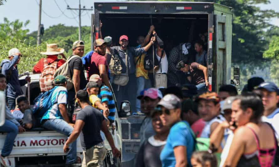 Hondurans head towards the US from San Pedro Sula in vans and trucks on 13 October.