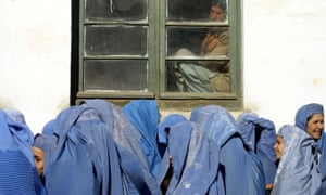 In February 2002, a man looks at Afghan women waiting to apply for jobs at Kabul's Ministry of Women, which initiated a drive to encourage professional women to re-enter the workforce after the demise of the Taliban.