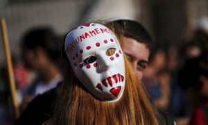 A woman wearing a mask with the slogan 'Not one less' embraces a fellow demonstrator during a protest against femicide outside Congress in the Argentinian capital Buenos Aires