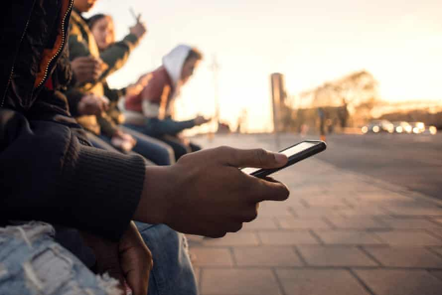 Midsection of teenager using phone while sitting with friends.