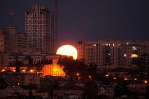 An unusual shot of the moon appearing wedged between buildings in Jerusalem, Israel