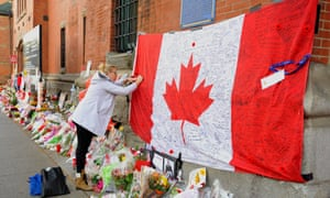 A woman signs a flag as people leave flowers at a memorial site outside the home base of the Argyll and Sutherland Highlanders at the John W. Foote Armoury in Hamilton, Canada.