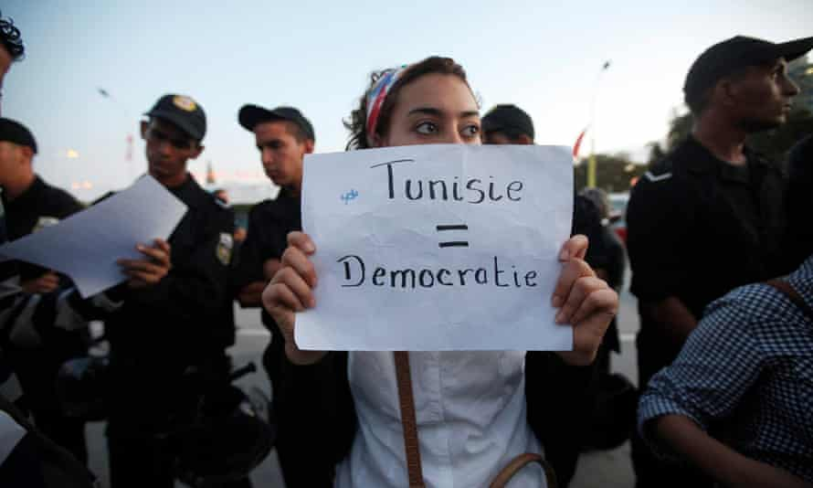 A Tunisian demonstrator holds a sign during a protest against the Islamist Ennahda movement in Tunis October 26, 2011.
