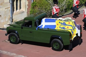 Coffin draped in flag on back of Land Rover