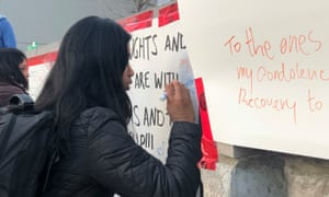 A woman writes a message at the memorial.