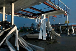 A car is trapped under the fallen metal roof of the Break Time gas station and convenience store in tornado-hit Jefferson City, Missouri on 23 May 2019
