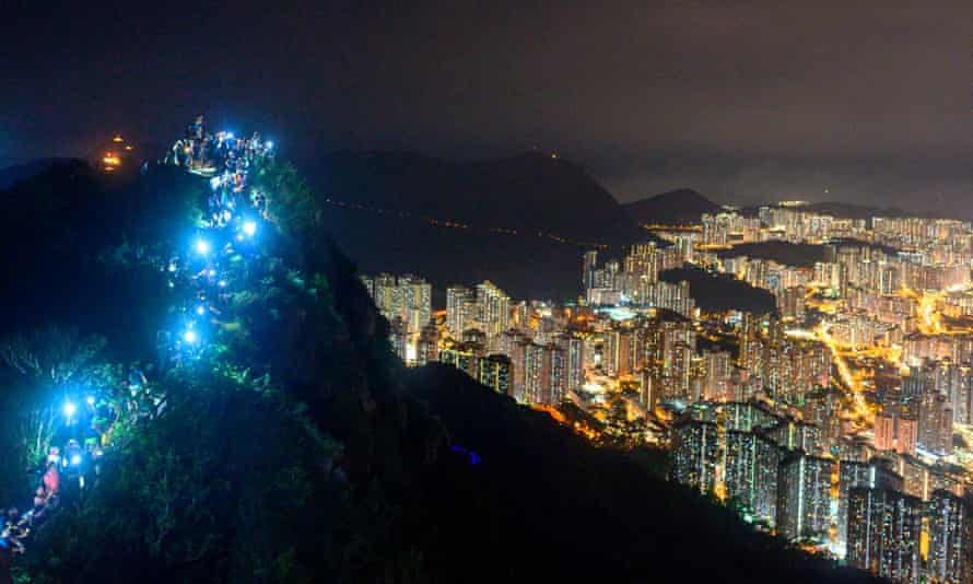 People light up mobile phones on top of Lion Rock.