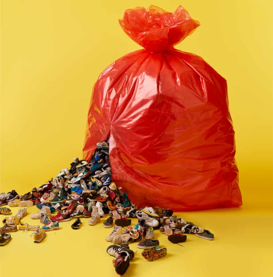 Red bin bag against yellow background, with trainers bursting out of it