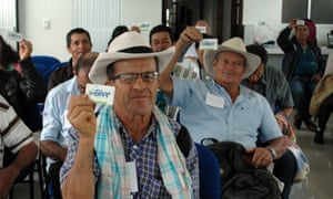 Colombian farmers hold up their Bive cards. Some 90% of those who get healthcare from Bive come from low-income households