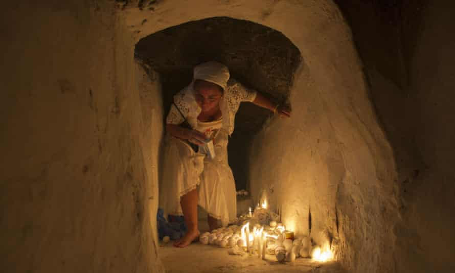 A woman leaves eggs inscribed with messages in a cave beneath the synagogue.