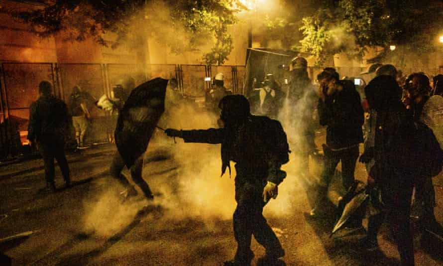 Protesters walk through chemical irritants dispersed by federal agents overnight on Wednesday.