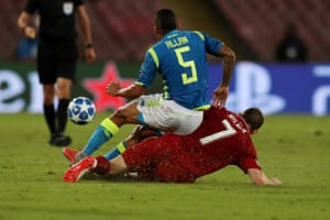 James Milner of Liverpool is booked for this challenge on Allan of Napoli.