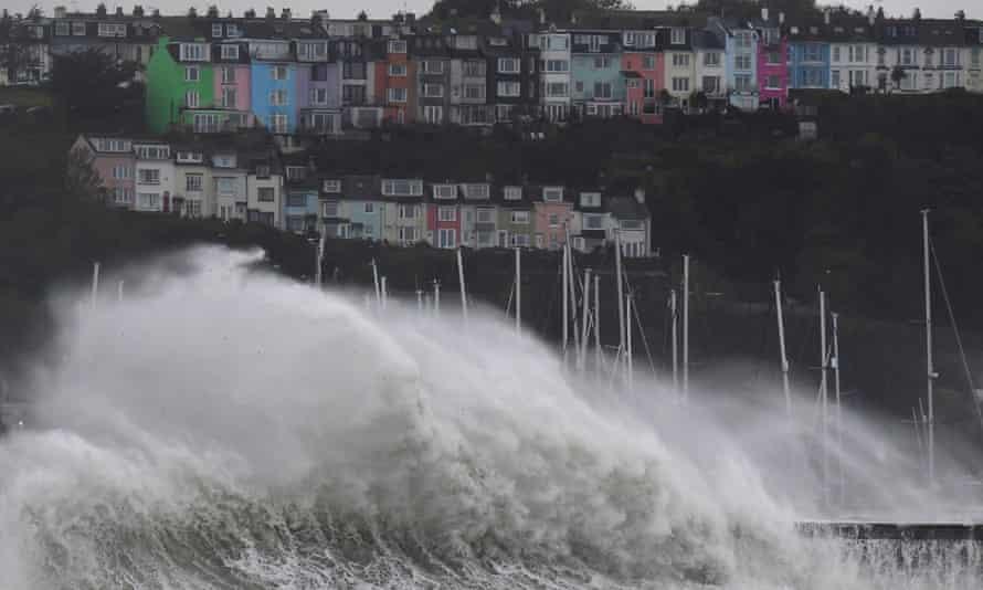 Large waves crash over the seawall in Brixham, Devon