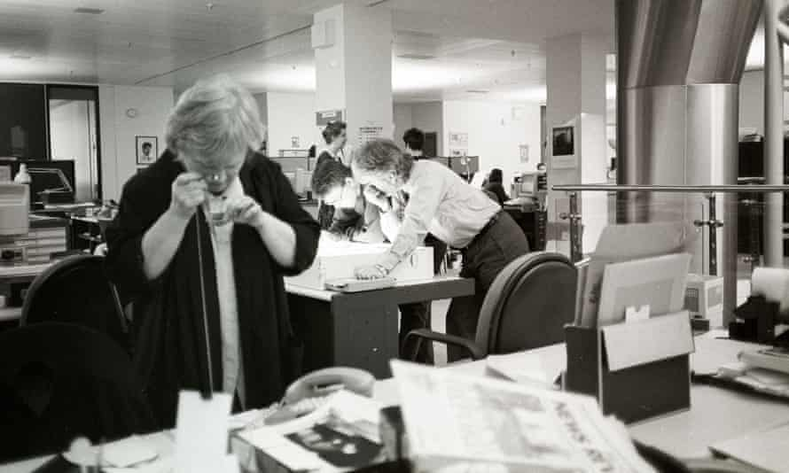 A black and white photograph of the Observer newsroom showing Jane Bown looking at a contact sheet with her monocle, with Tony McGrath leaning over a desk in the background