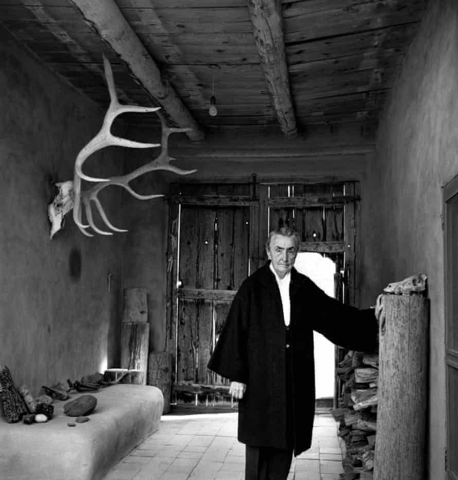Georgia O'Keeffe  in 1967 at the entrance of her New Mexico home, wearing a big coat, with an elk horn hanging on the wall and bones on a shelf