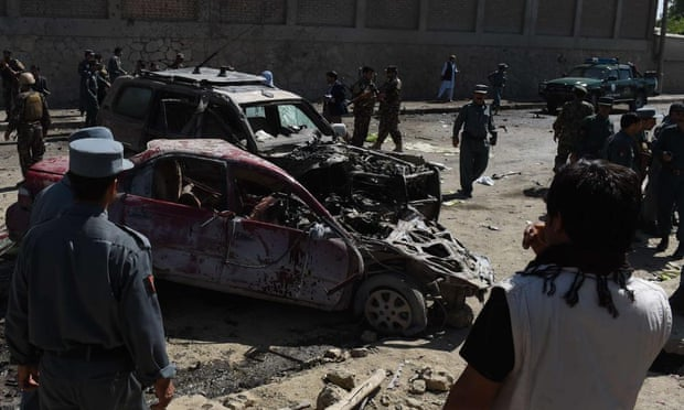 Afghan and foreign security forces inspect the site of a suicide attack in Kabul on Sunday.