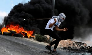 A Palestinian protester uses a slingshot to hurl stones at Israeli troops in the Israeli-occupied West Bank.