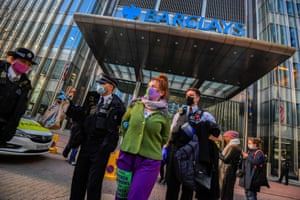 Police officers detain an activist from the Extinction Rebellion, a global environmental movement, outside the Barclays offices in Canary Wharf, London, Britain, April 7, 2021.