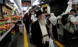 People wear face masks as they shop in a main market in Jerusalem