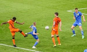 Georginio Wijnaldum of the Netherlands (left) shoots on target.