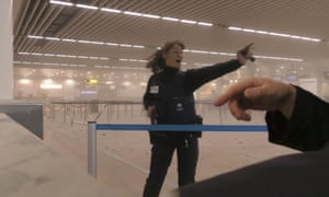 A police officer directs passengers in a smoke filled terminal at Brussels airport after the explosions