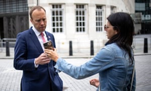 Health secretary Matt Hancock looks at the phone of his aide Gina Coladangelo as they leave the BBC in central London on 6 June, 2021.