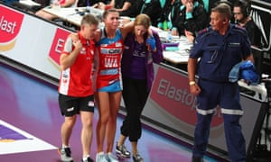 Maddy Proud being helped off court by Swifts and Firebirds physios.