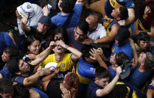 Boca Juniors fans celebrate their team's goal as they watch on TV in Buenos Aires.