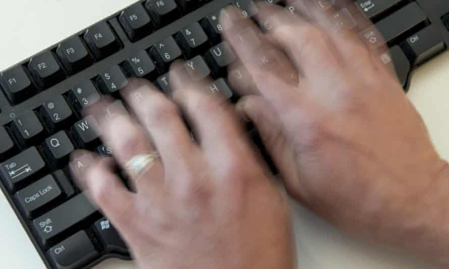 A man types on a computer keyboard.