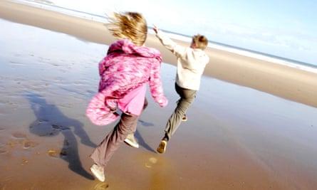 children skipping on a sunny beach