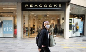 A woman wearing a face covering walks past a Peacocks store in Cardiff last month.