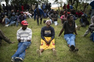Homeless people wait for food parcels in a Johannesburg park