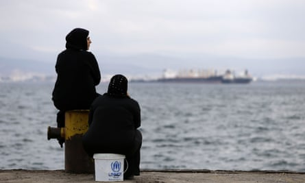 Two women sit on a dock at a refugee camp that houses 3,200 people in a western suburb of Athens