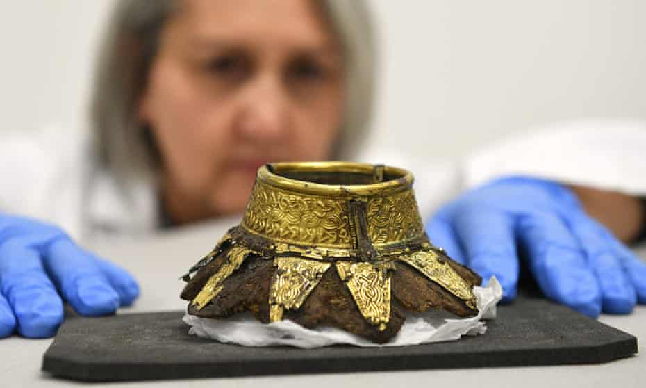 conservator Claire Reed, inspecting the remains of a wooden drinking vessel with a decorated gold neck
