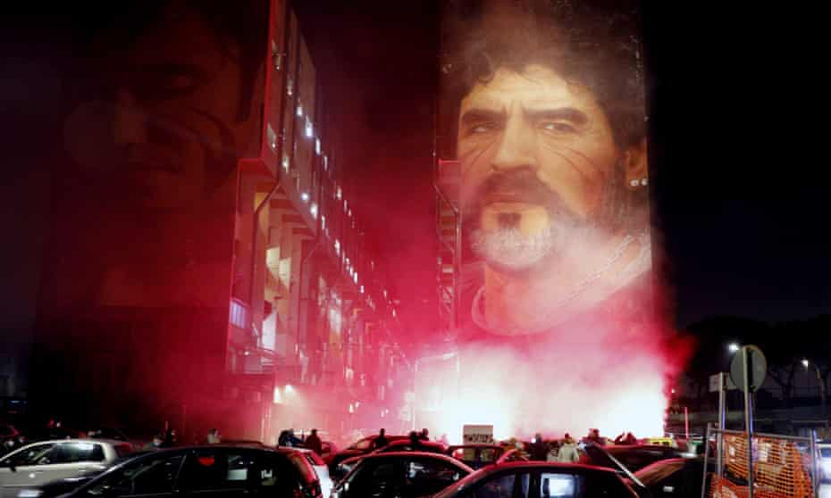 People light flares as they gather under a mural of Diego Maradona in Naples.