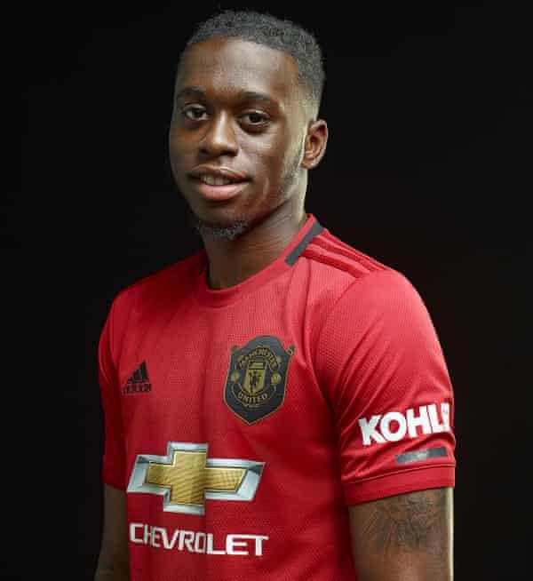 Wan-Bissaka poses after signing for United.