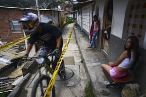 Residents watch as a downhill rider competes during the Adrenalina Urban Bike race final