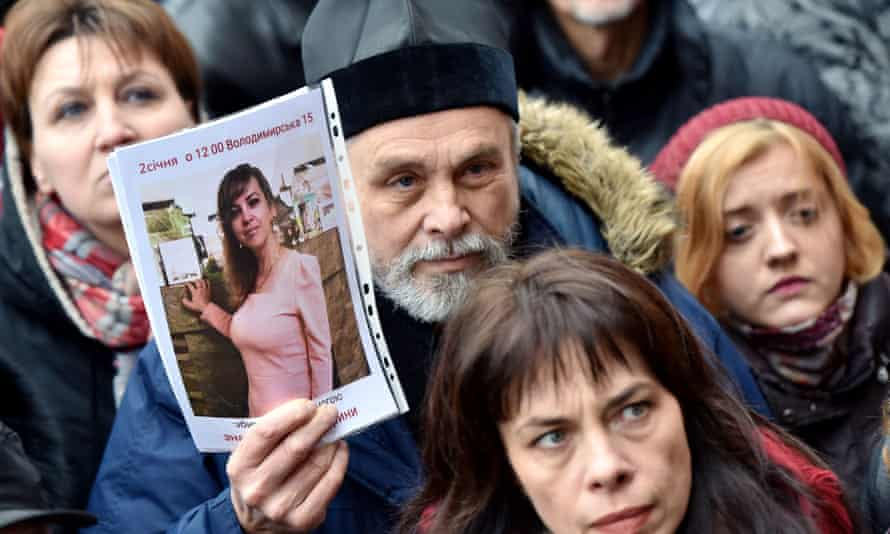 An Orthodox priest holds a picture of Iryna Nozdrovska during a protest outside Kiev police HQ against the murder of the Ukrainian lawyer who helped convict her sister's well-connected killer.
