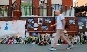 A pedestrian walking past flowers left outside Finsbury Park mosque in north London following the nearby van attack.