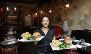 Waiter in French restaurant carrying plates of burgers