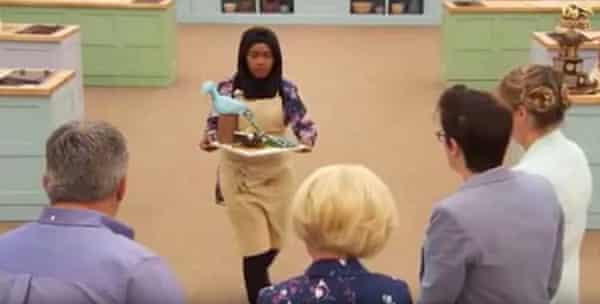 Nadiya brings her chocolate peacock up to the judging table.