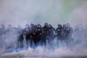 Police officers veiled in teargas