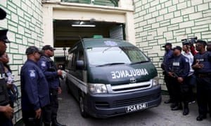 Police stand guard as an ambulance leaves the state prison in Port-of-Spain on Thursday. According to local media Jack Warner left jail in Trinidad and Tobago via ambulance